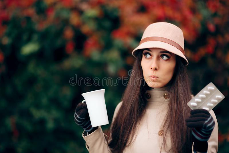 Woman Holding Tea Mug and Pills Treating a Cold in Autumn Season royalty free stock photos