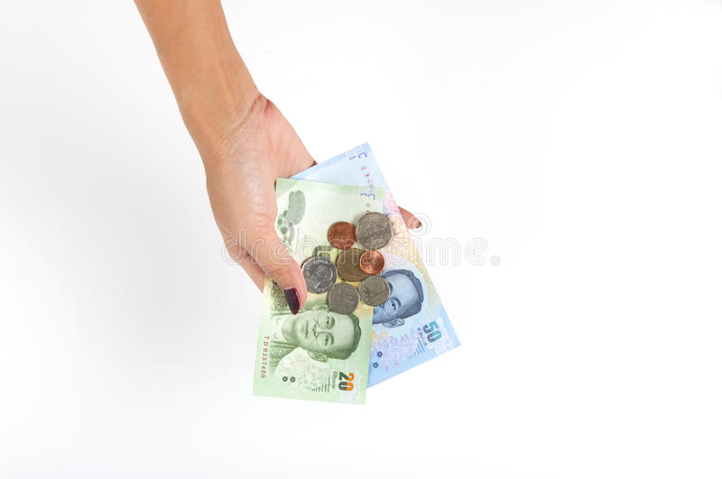 Woman holding Thailand Baht. Woman holding coins and banknotes of Thailand Baht isolated on white royalty free stock image