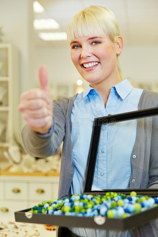 Woman holding thumbs up in jewelry stock images
