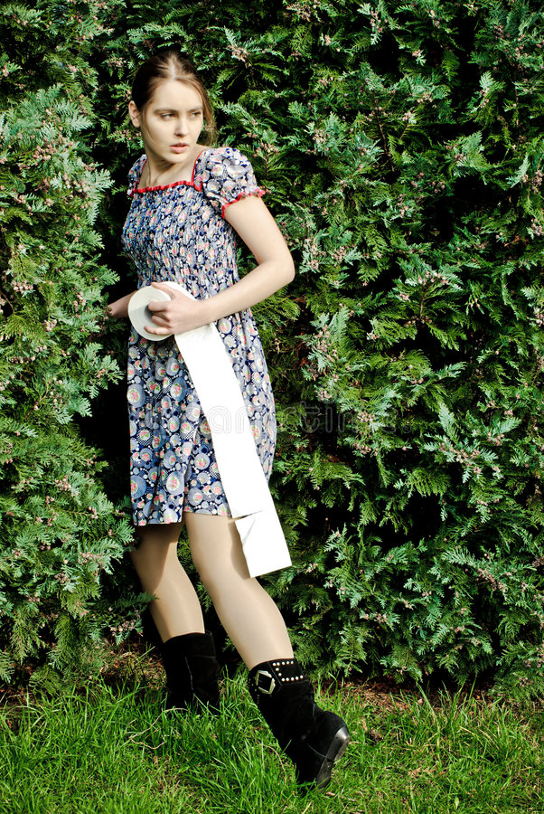Woman holding toilet paper. A view of a young woman holding a roll of toilet paper about to go behind a tall hedge stock photos
