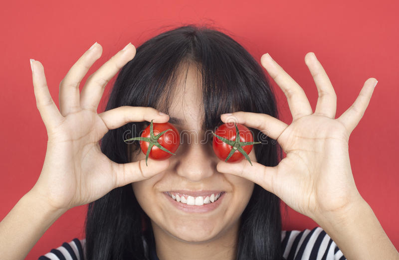 Woman holding tomato over eyes stock images