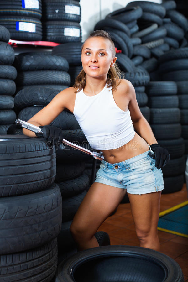 Woman holding tool in hands and working with auto in service poi stock photos
