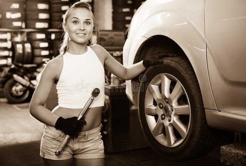 Woman holding tool in hands and working with auto in service poi stock photo