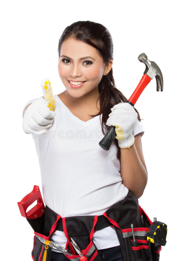 Woman holding tool showing thumb up. Portrait of young asian woman with hammer showing thumb up isolated over white background stock photo