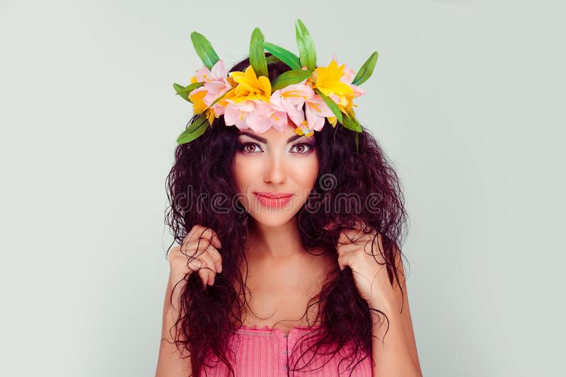Woman holding touching her curly hair with both hands stock image