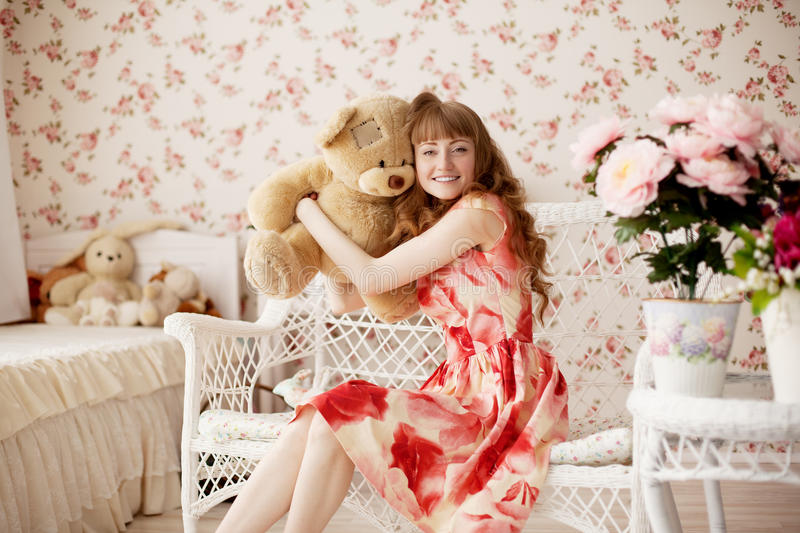 Woman holding a toy bear in a nursery royalty free stock photography