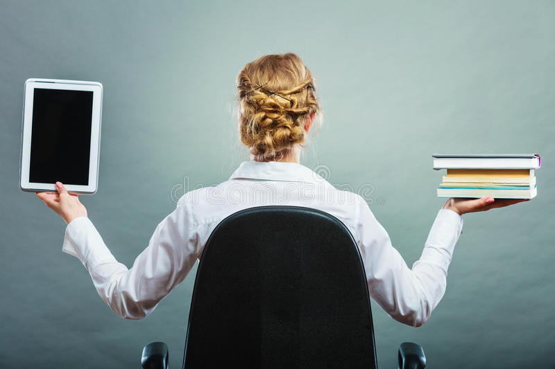 Woman holding traditional book and e-book reader. Ebook vs book. Woman sitting on chair holding traditional book and e-book reader tablet touchpad pc back view stock photos