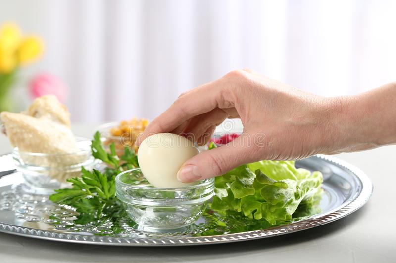 Woman holding traditional egg over Passover Pesach Seder plate on table. Closeup stock photo