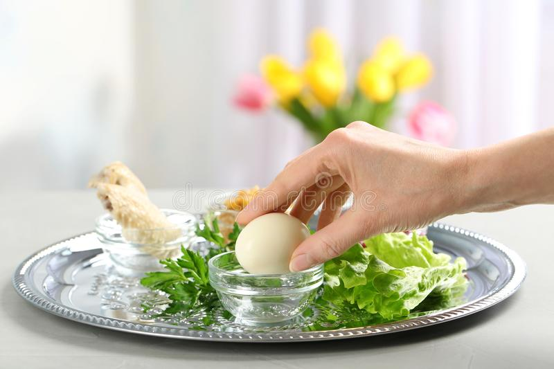 Woman holding traditional egg over Passover Pesach Seder plate on table, closeup. royalty free stock image