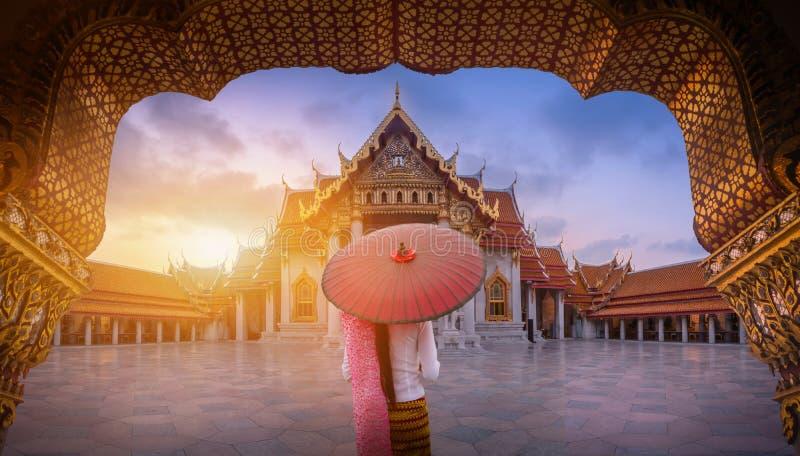 Woman holding traditional red umbrella on the Marble Temple, Wat Benchamabopitr Dusitvanaram at sunrise in Bangkok, Thailand. royalty free stock photos