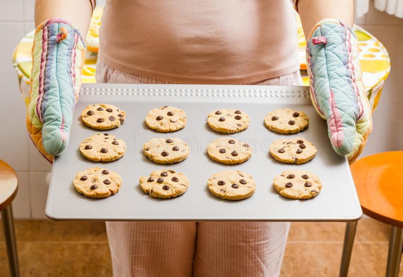 Woman holding a tray with baked cookies with kitch royalty free stock photo