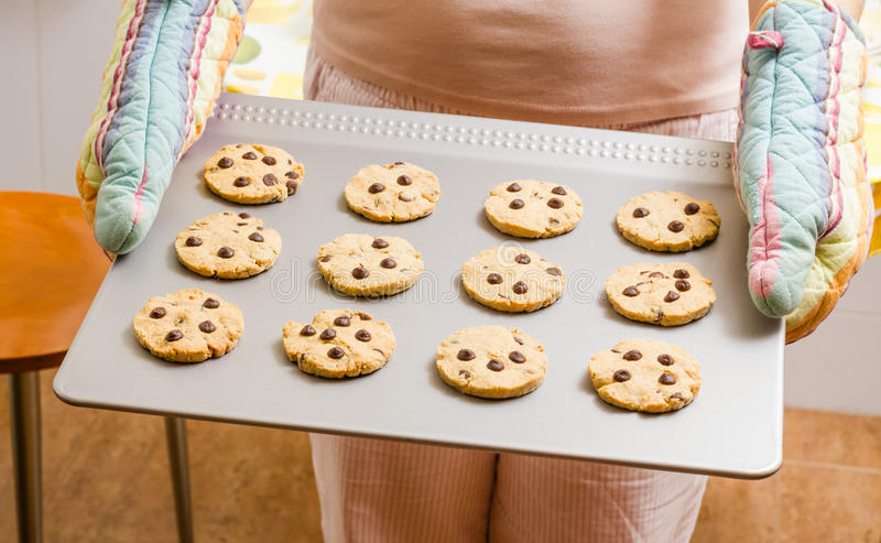 Woman holding a tray with baked cookies with kitchen gloves stock photography