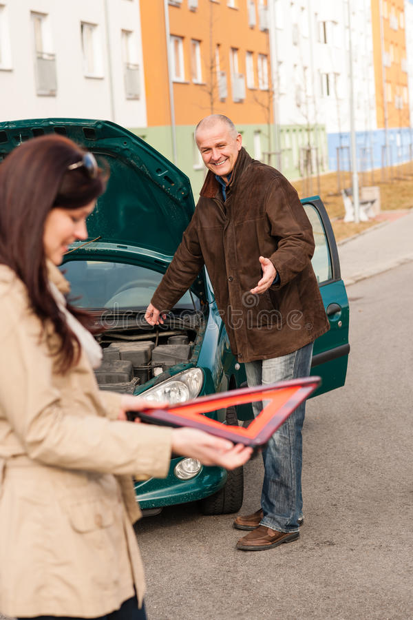 Download Woman Holding Triangle Sign Repairman Fixing Car Stock Photo - Image: 26886238