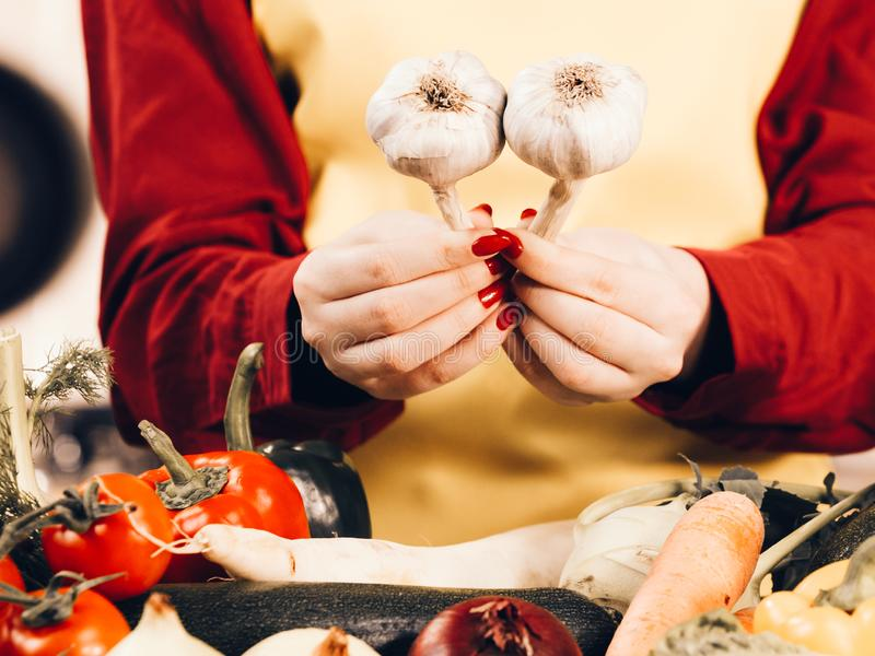 Woman holding two garlic. Woman holding healthy herb, two fresh natural garlic. Healthy eating and dieting concept royalty free stock photography