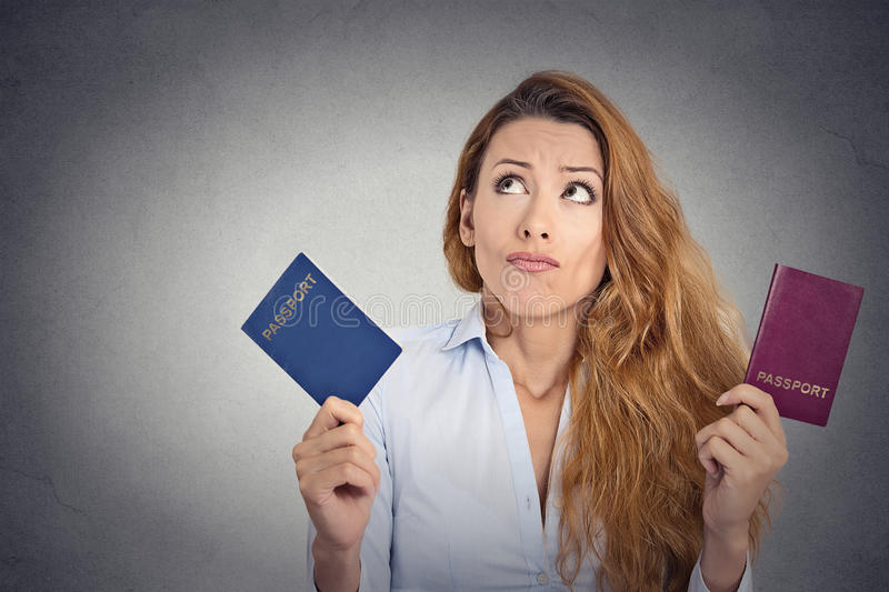 Woman holding two passports confused face expression. Portrait young woman holding two passports confused face expression on grey wall background royalty free stock image
