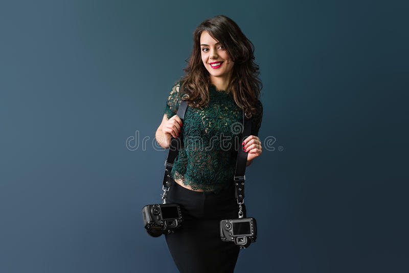 Woman holding two photographic cameras. On a dark blue stock images