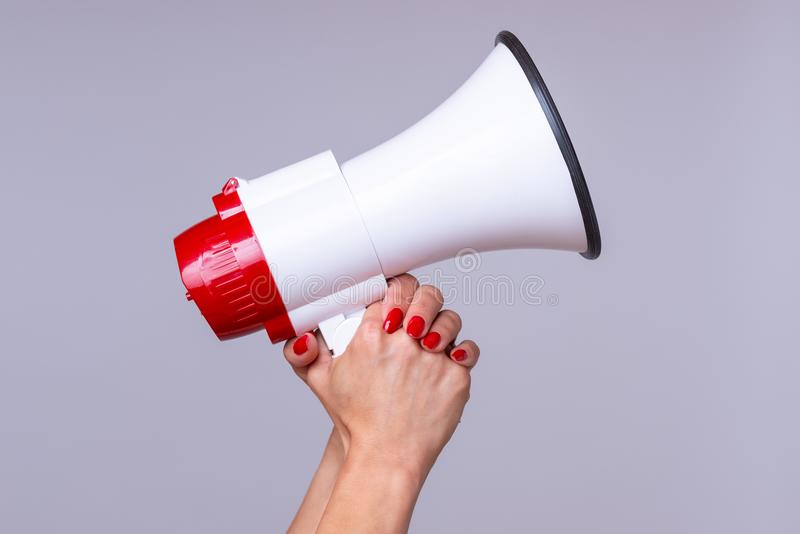 Woman holding up a loud hailer or megaphone. Woman holding up a loud hailer, bullhorn or megaphone as she prepares to stage a protest or demonstration to air her royalty free stock images