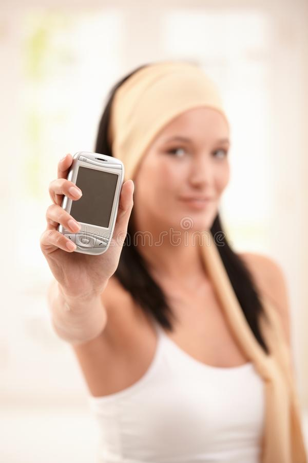 Woman holding up mobile phone in focus