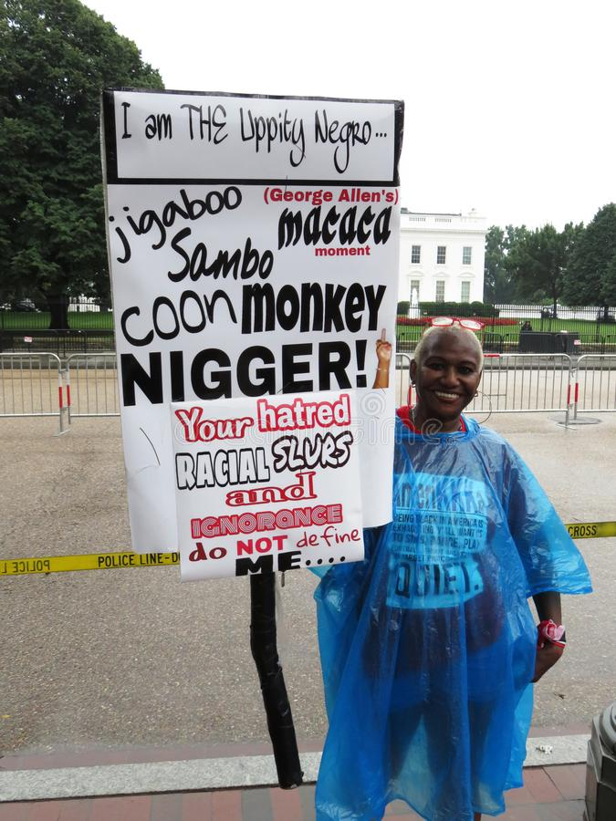 Woman Holding up Protest Sign Against Racial Slurs stock images