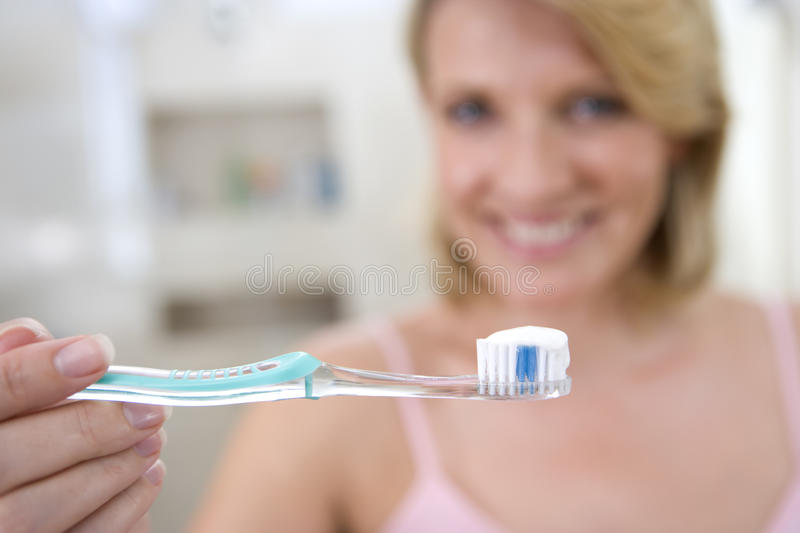 Woman holding up toothbrush, smiling, portrait (focus on toothbrush) stock photo