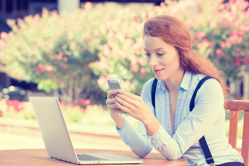 Woman holding, using smart, mobile phone and computer royalty free stock image