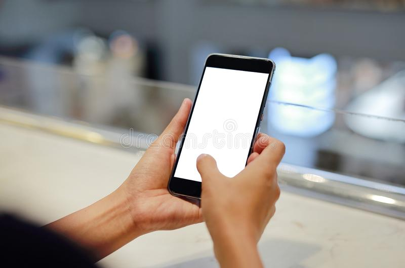Woman holding and using smartphone with blank white screen in cafe stock image