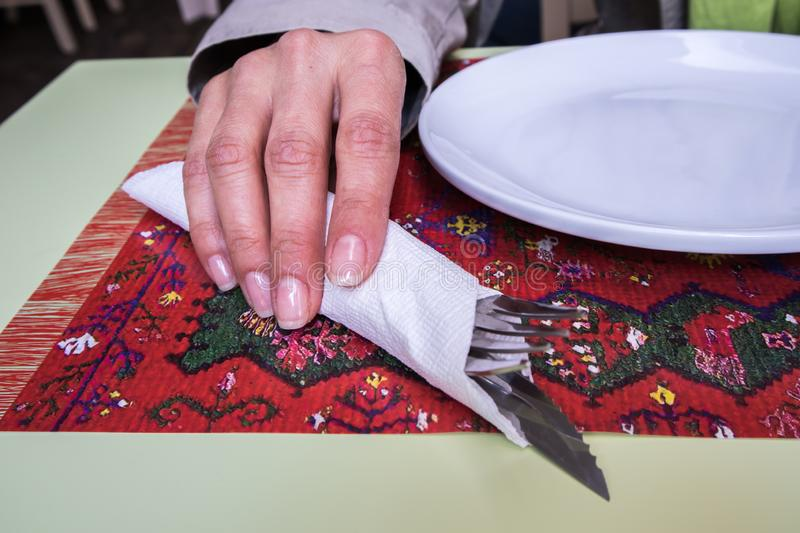 Woman holding utensil in restaurant. M closeup, single, caucasian, knife and fork royalty free stock photography