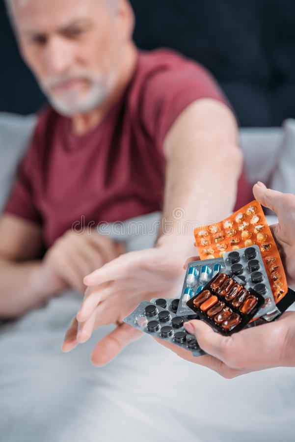 Woman holding various pills for sick husband in hands royalty free stock image