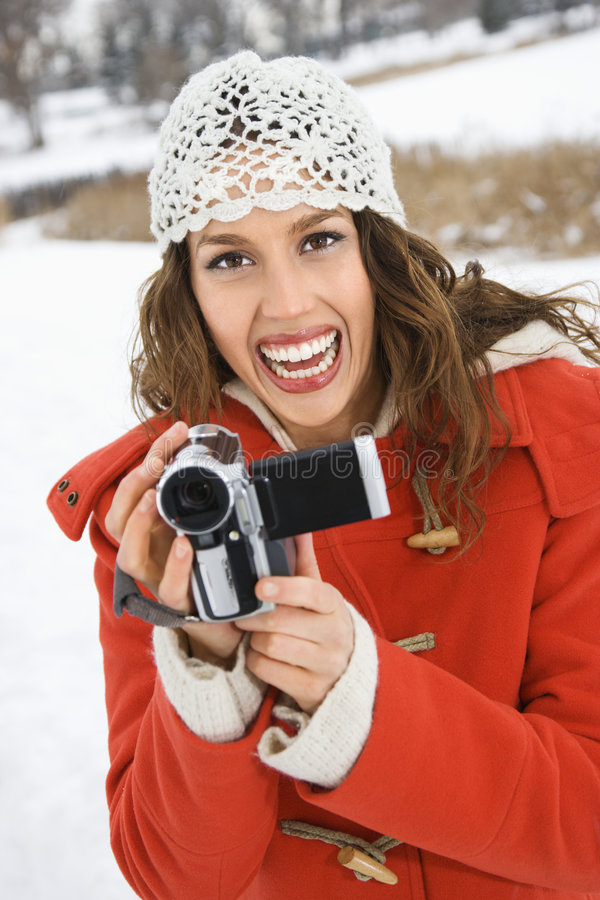 Woman holding video camera. Caucasian young adult female in winter clothing holding video camera and smiling at viewer stock photography