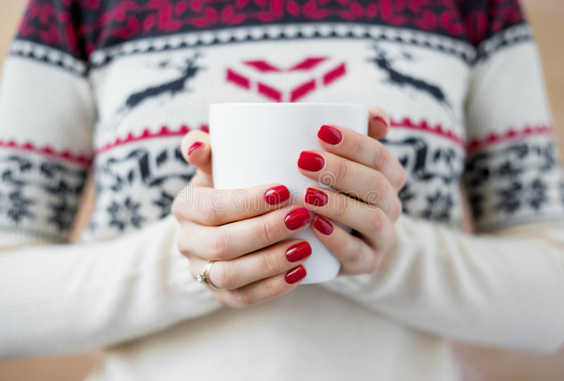 Woman holding warm cup of tea. In her hands royalty free stock photos