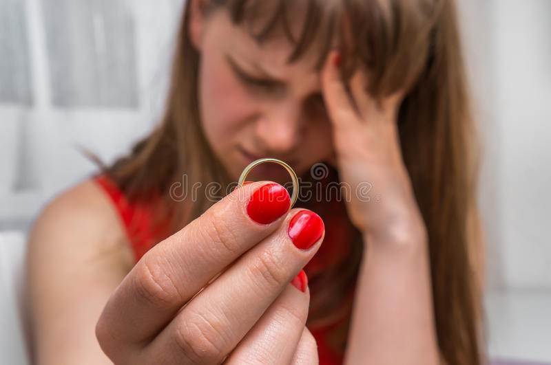 Woman is holding wedding ring - divorce concept stock photography