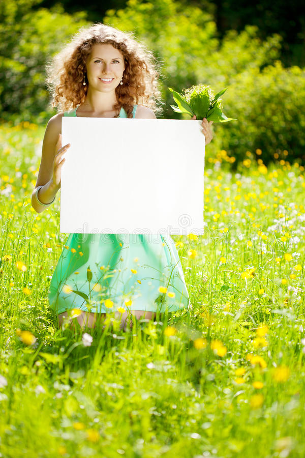 Woman holding white blank poster in summer park royalty free stock photos