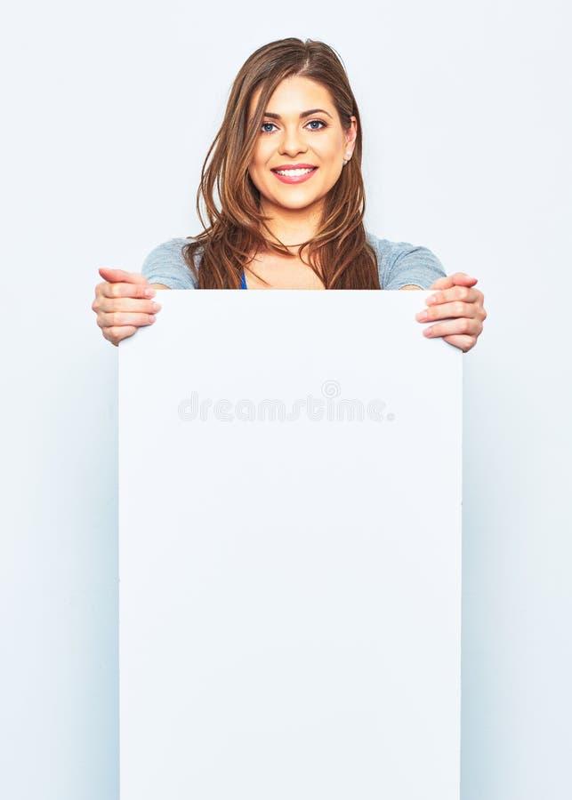 Woman holding white blank signboard. Smiling female model against white studio background royalty free stock image