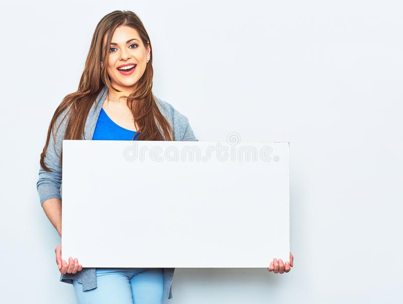 Woman holding white blank signboard. Smiling female model against white studio background stock photos