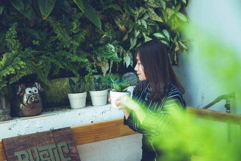 Woman Holding White Clay Pot With Green Plant Sitting Near White Painted Wall stock images