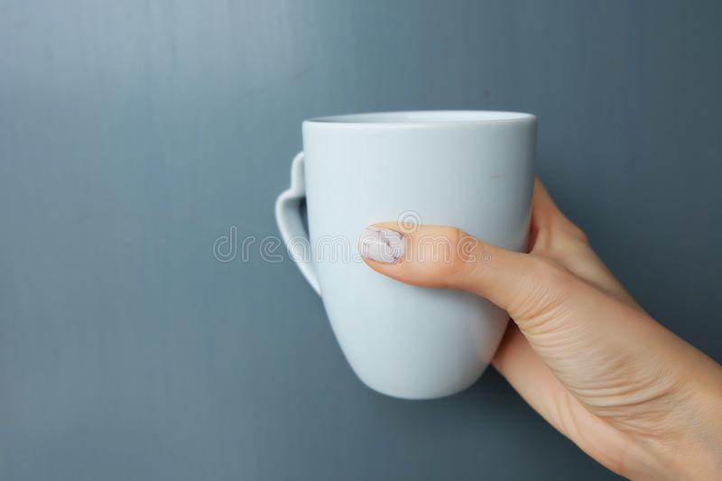 Woman Holding White Cup of Coffee. Close Up Granite Gray Nail Polish on the Background royalty free stock images