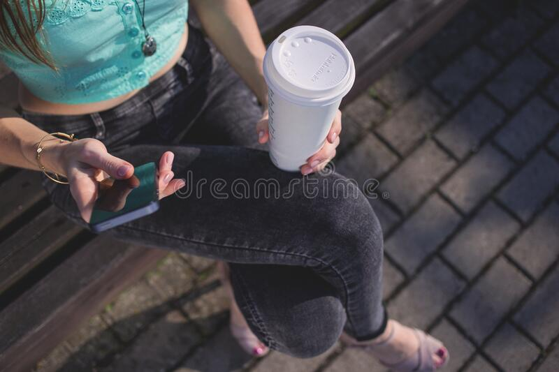Woman Holding White Disposable Cup and Smartphone stock images