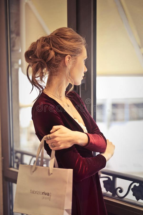 Woman Holding White Paper Bag While Looking at the Window royalty free stock photography