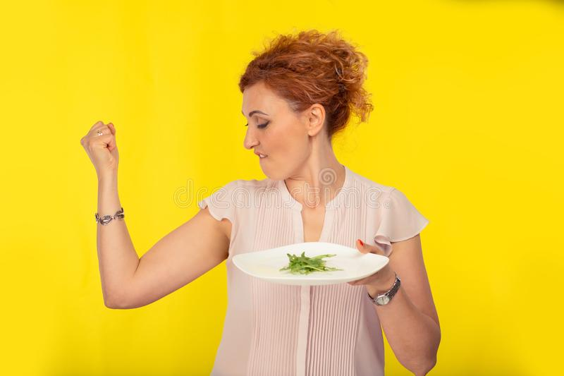 Woman holding a plate with green salad showing muscles royalty free stock image