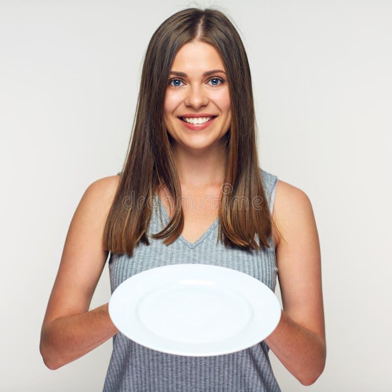 Woman holding white plate. Smiling girl waitress royalty free stock image