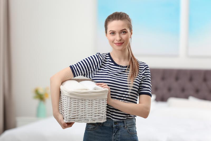 Woman holding wicker basket with folded clean towels in bedroom stock photo