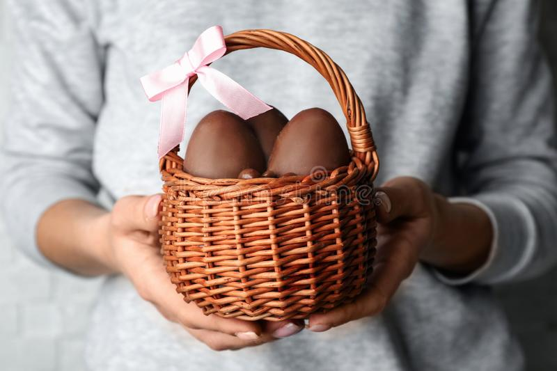 Woman holding wicker basket with sweet chocolate Easter eggs stock photo