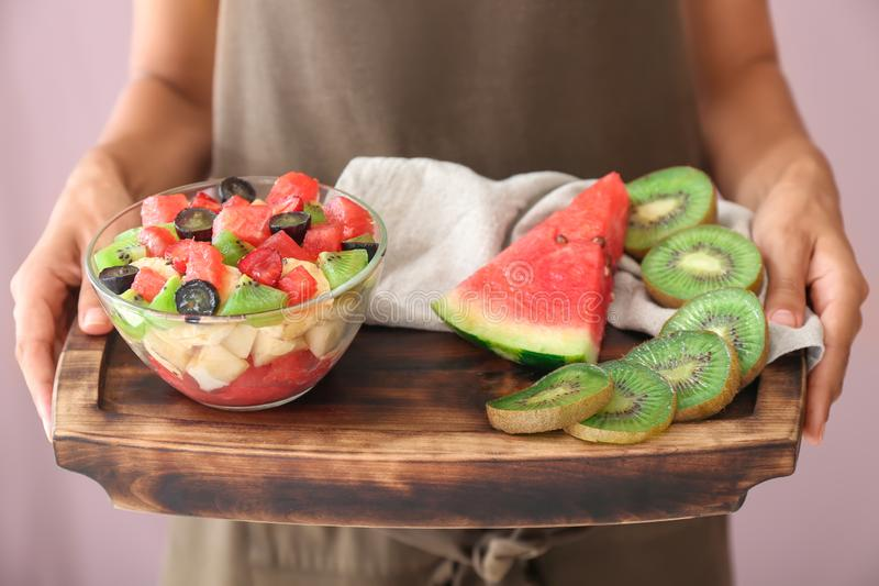 Woman holding wooden board with delicious watermelon salad and fruits, closeup stock photography