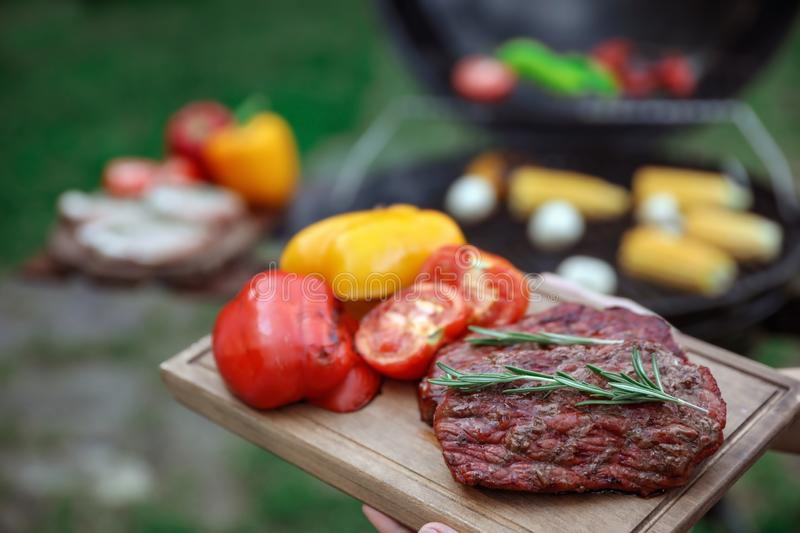 Woman holding wooden board with grilled vegetables and steak outdoors. Summer barbecue stock photos