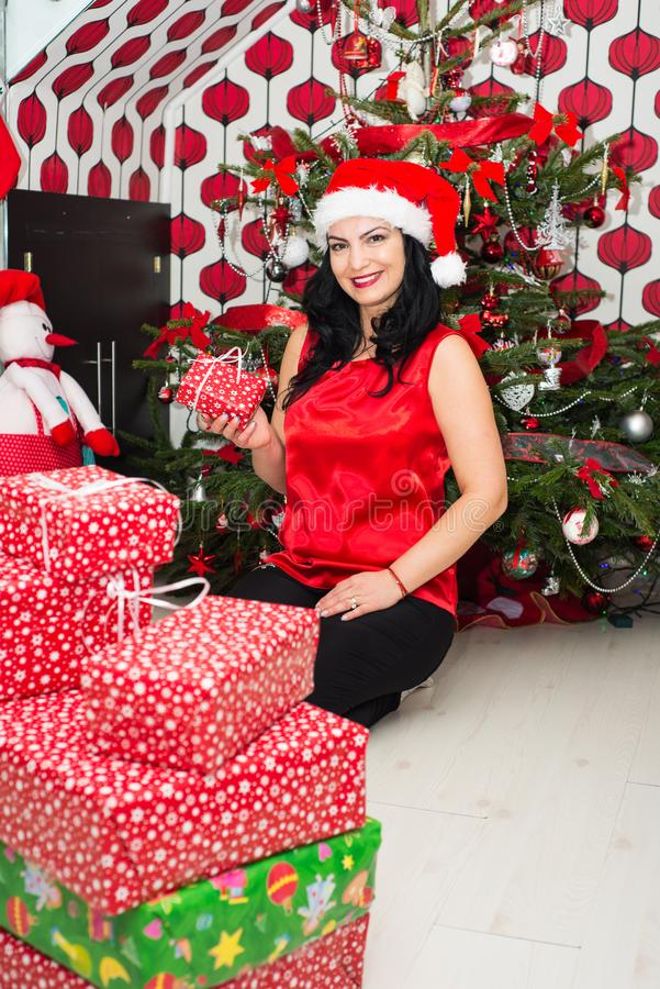 Woman holding Xmas present. Cheerful woman holding little Christmas gift in front of tree in her home royalty free stock photography