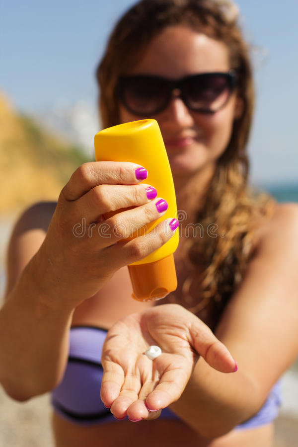 Woman is holding yellow tube with sunscreen tan stock images