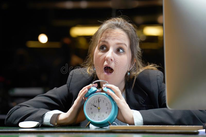 Woman holding a clock. Woman holds an alarm clock in her hand in the workplace stock image