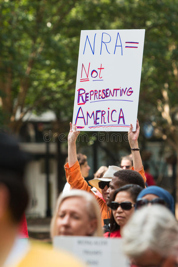 Woman Holds Anti NRA Sign At Atlanta Political Rally. Atlanta, GA, USA - April 29, 2017: A woman holds up a sign that says `NRA = Not Representing America` at a stock photos