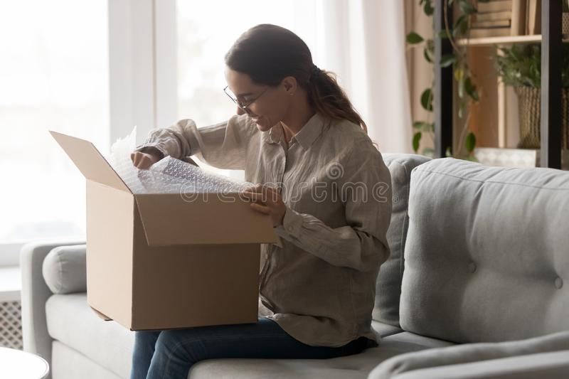 Woman holds big carton box on laps unpack delivered goods stock photo