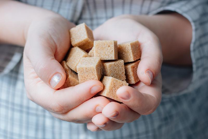 Woman holds brown sugar cubes in hands. royalty free stock images